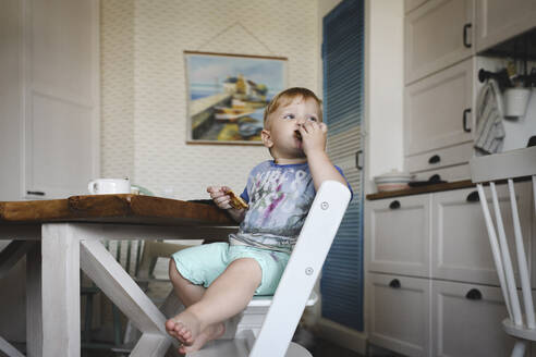 Russia, Moscow, little cute blondie boy with pan-cakes on the kitchen - EYAF00350