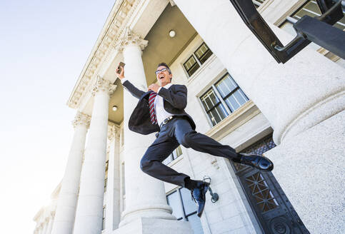 Mixed race businessman jumping for joy outside courthouse - BLEF12592