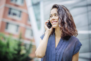 Mixed race businesswoman talking on cell phone outdoors - BLEF12802