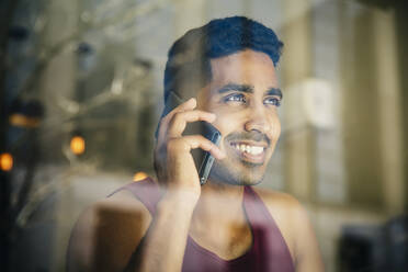 Indian man talking on cell phone in cafe - BLEF12811