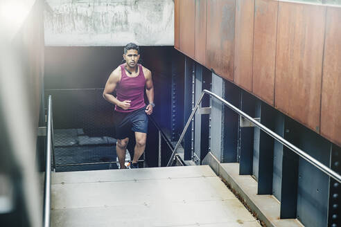 Indian man jogging on city steps - BLEF12814