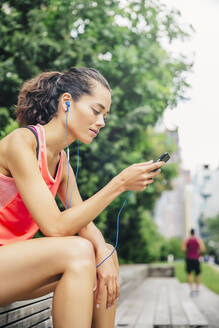 Indian athlete listening to mp3 player in city - BLEF12820