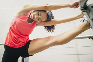 Mixed race athlete stretching on banister - BLEF12829