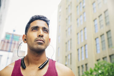 Indian athlete listening to earbuds in city - BLEF12832