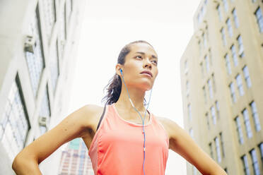Mixed race athlete listening to earbuds in city - BLEF12835