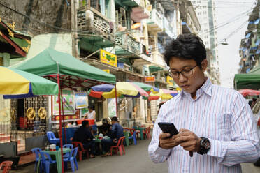 Asian businessman using cell phone in city - BLEF12940