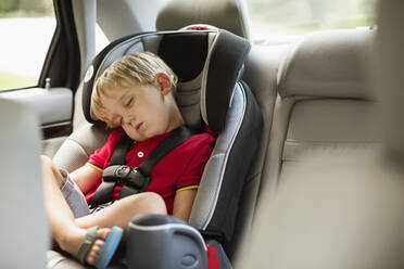 Caucasian boy napping in car seat - BLEF12961