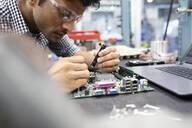 Focused male engineer assembling circuit board in research lab - HEROF37396