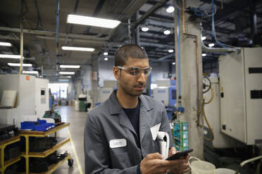 Male machinist using smart phone in factory - HEROF37459