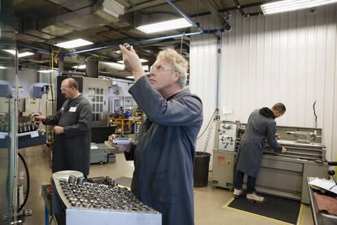 Male machinist examining equipment in factory - HEROF37519