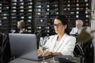 Businesswoman working at laptop in wine bar - HEROF37585