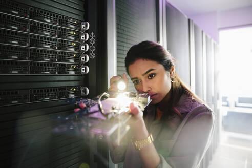 Female IT technician examining equipment in network server room - HEROF37861