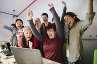 Excited computer programmers cheering at laptop in conference room meeting - HEROF37885