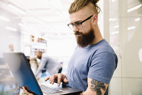 Creative businessman with tattoos using laptop in office - HEROF37918