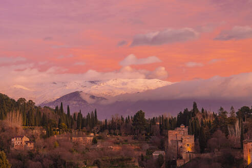 View of Alhambra with mountain Sierra Nevada in the background at sunset, Granada, Spain - TAMF01865