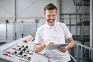 Smiling man using tablet at control panel in a factory - BSZF01157