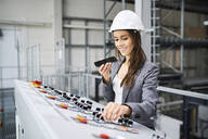Woman wearing hard hat at control panel in a factory using cell phone - BSZF01175