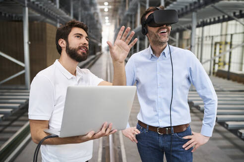 Man with laptop and businessman wearing VR glasses in factory - BSZF01184