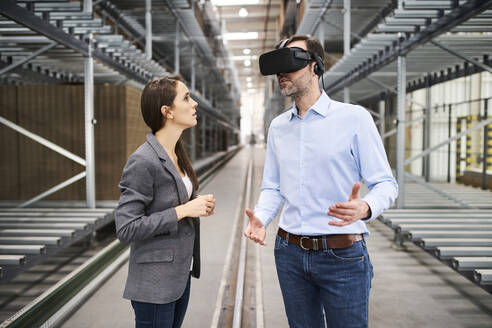 Businesswoman talking to businessman wearing VR glasses in factory - BSZF01190