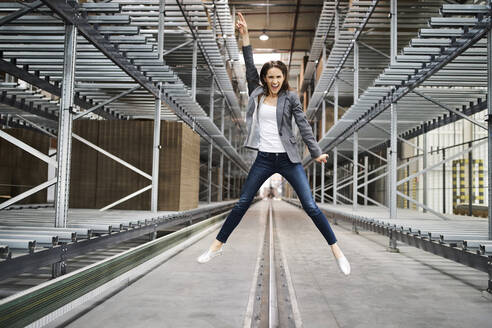 Excited businesswoman jumping in factory - BSZF01208