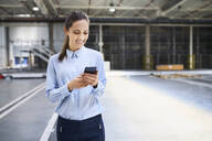 Smiling businesswoman using cell phone in a factory - BSZF01223