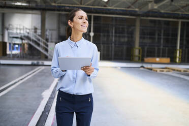 Smiling businesswoman using tablet in a factory - BSZF01226