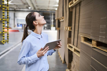 Businesswoman with tablet in a factory warehouse checking stock - BSZF01229