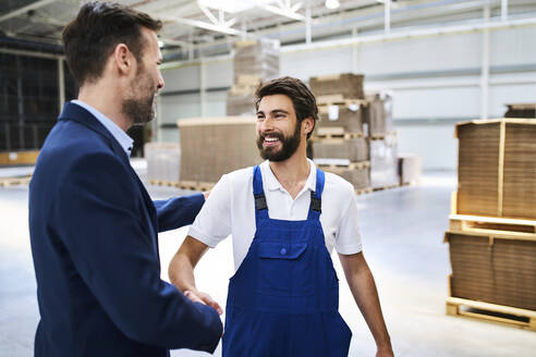 Businessman and worker shaking hands in a factory - BSZF01241
