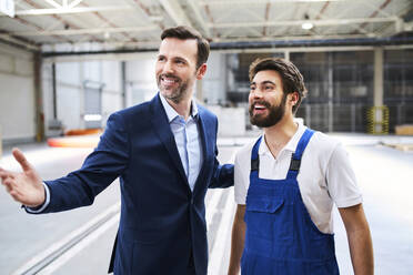 Happy businessman and worker in a factory - BSZF01244