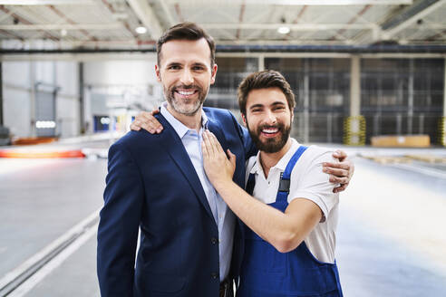 Portrait of happy businessman and worker in a factory - BSZF01247