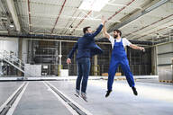 Excited businessman and worker jumping and high fiving in a factory - BSZF01250
