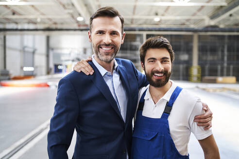 Portrait of happy businessman and worker in a factory - BSZF01253
