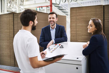 Business people and employee talking in a factory - BSZF01262