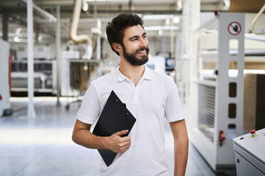 Smiling employee holding clipboard in a factory - BSZF01265