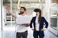 Man with laptop and businesswoman wearing VR glasses in factory - BSZF01277