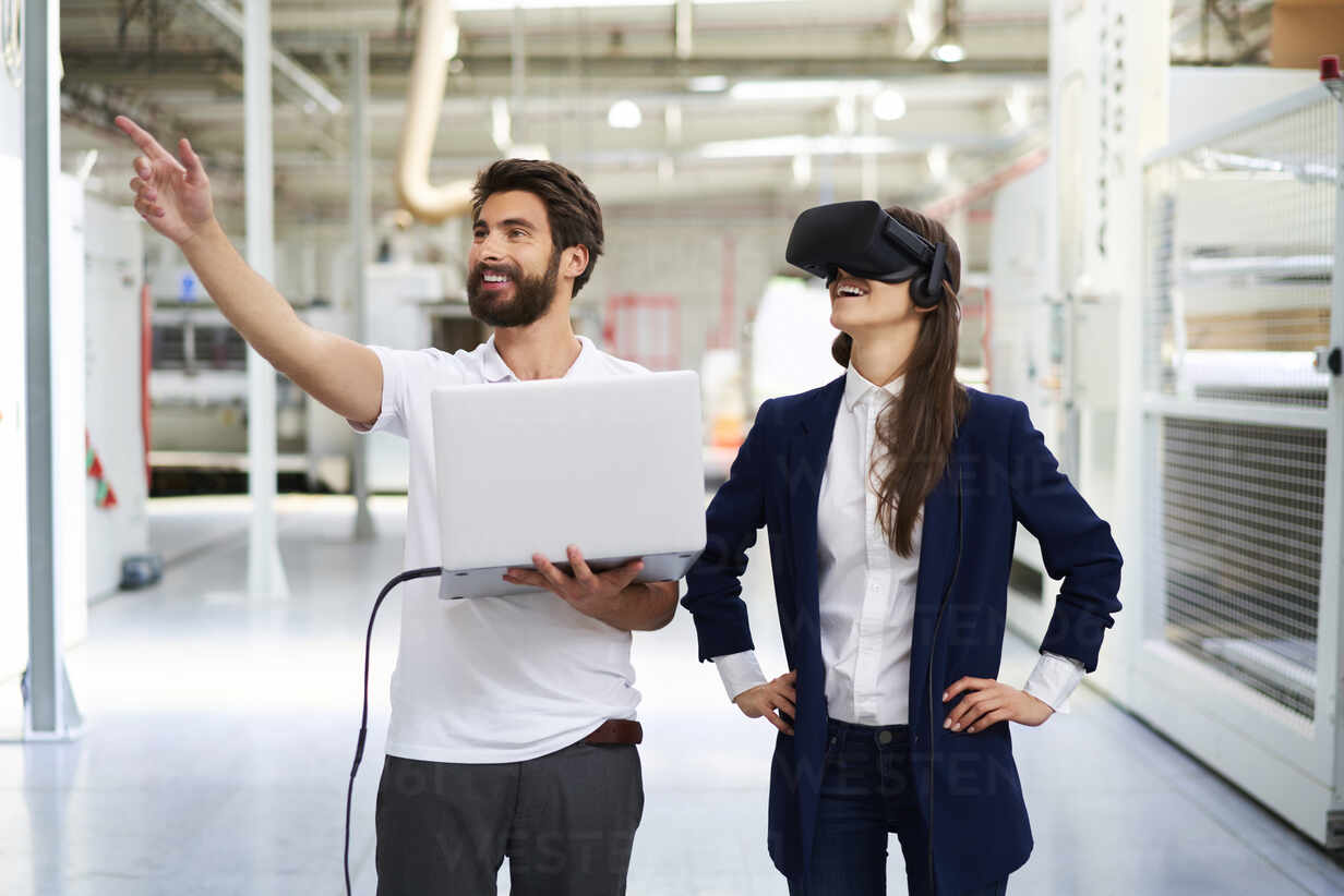Man with laptop and businesswoman wearing VR glasses in factory - BSZF01277 - Bartek Szewczyk/Westend61