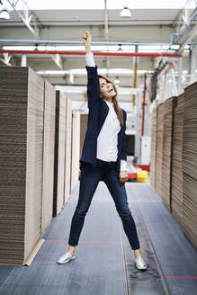 Portrait of excited businesswoman in factory warehouse - BSZF01286