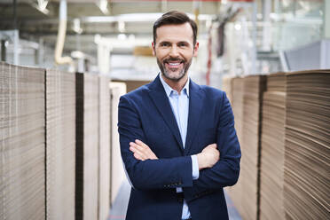Portrait of smiling businessman in factory warehouse - BSZF01289