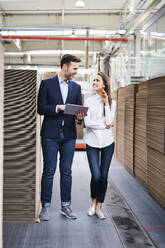 Businessman with tablet and woman talking in factory warehouse - BSZF01292