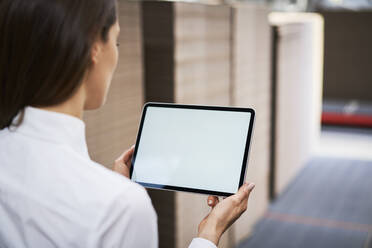 Close-up of woman using tablet in a factory warehouse - BSZF01295