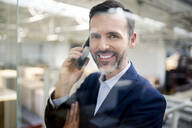 Portrait of smiling businessman on cell phone behind glass pane in a factory - BSZF01304