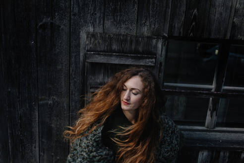 Portrait of redheaded woman with closed eyes, wooden wall in the background - OGF00086
