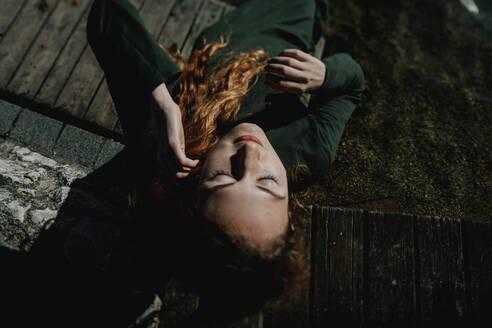 Portrait of redheaded woman lying - OGF00089