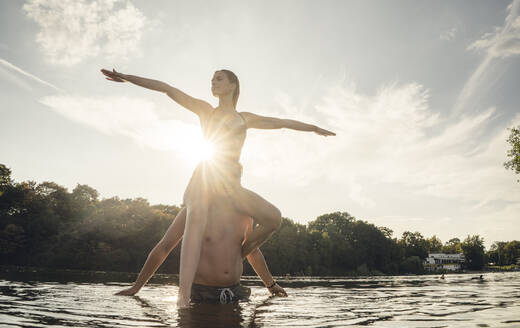 Young woman sitting on shoulders of young man standing in lake, enjoying the sun - GUSF02308