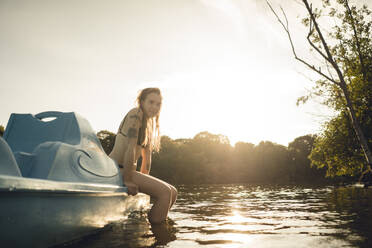 Young woman relaxing on the lake, sitting on boat - GUSF02311