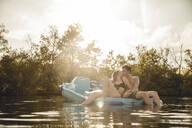 Young couple sitting on a boat on the lake, kissing - GUSF02344