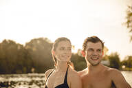 Young couple with drink umbrellas in their hair, having fun at the lake - GUSF02347