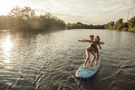 Young couple enjoying summer at the lake, standing on a paddleboard - GUSF02353