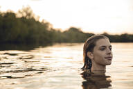 Young woman swimming in lake at sunset - GUSF02362