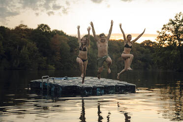Friends having fun at the lake, jumping from bathing platform - GUSF02368